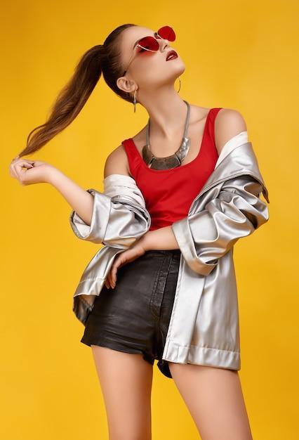 Elegantes glamour-hipster-girl im roten top, schwarzen shorts und jeansjacke Premium Fotos