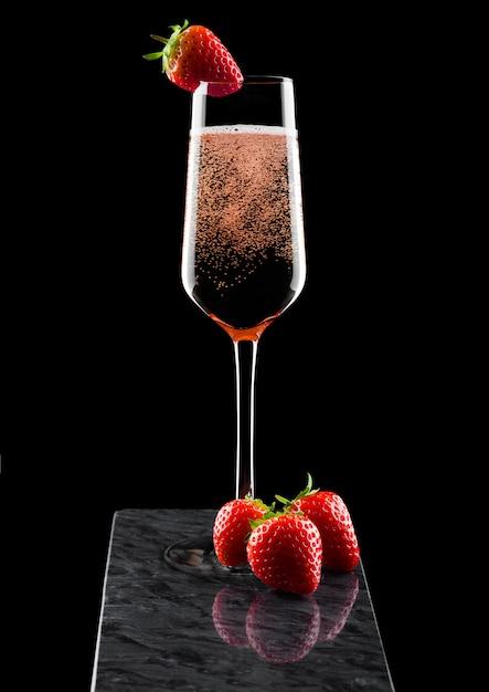 Elegantes glas rosa rosenchampagner mit erdbeere oben und frischen beeren auf schwarzem marmorbrett auf schwarz. Premium Fotos