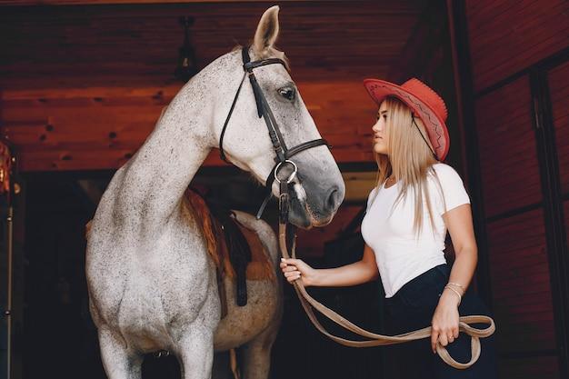 Elegantes mädchen in einem bauernhof mit einem pferd Kostenlose Fotos