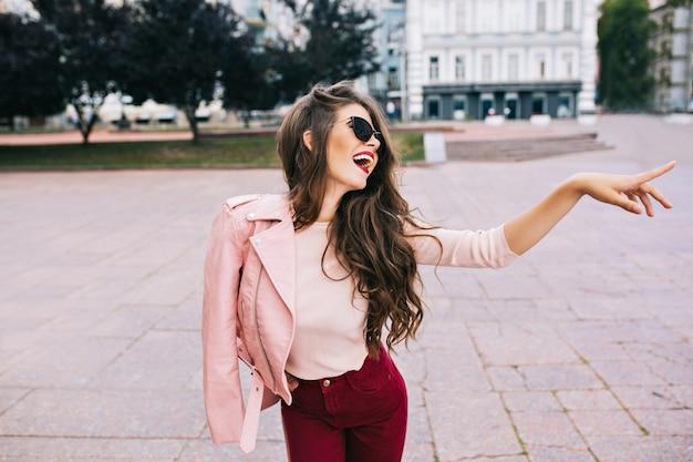 Elegantes mädchen mit langer frisur in weinigen hosen, die spaß in der stadt haben. sie hat eine rosa jacke auf der schulter und zeigt sich zur seite. Kostenlose Fotos