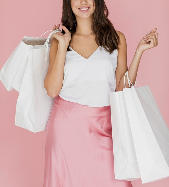 Elegantes mädchen mit rosa rock und vielen einkaufstüten Kostenlose Fotos