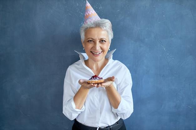 Elegantes mittleres alter im weißen hemd, das jubiläum feiert, das lokal mit frisch gebackenem kuchen posiert, freudigen gesichtsausdruck habend Kostenlose Fotos