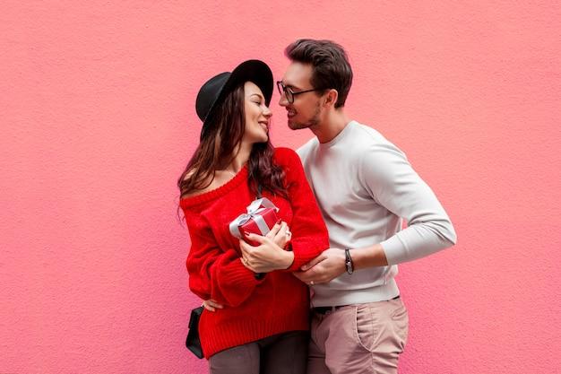 Elegantes stilvolles paar in der liebe händchen haltend und einander mit vergnügen ansehend. langhaarige frau im roten strickpullover mit ihrem freund posiert. Kostenlose Fotos