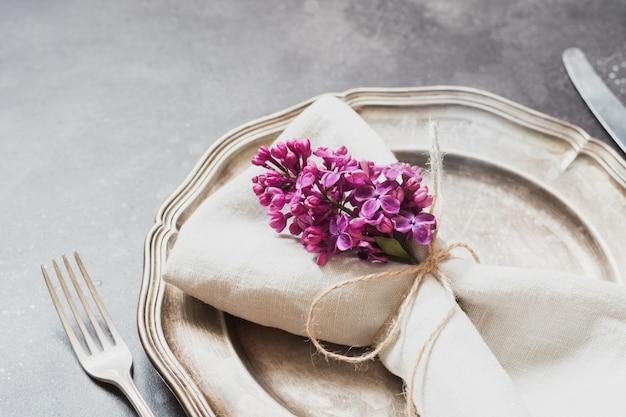 Elegantes tabellengedeck des frühlinges mit violetter flieder, tafelsilber auf weinlesetabelle. Premium Fotos
