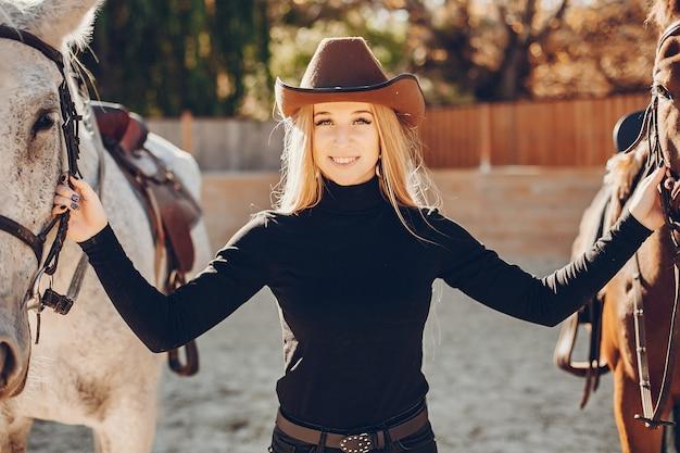 Elegants mädchen mit einem pferd in einer ranch Kostenlose Fotos