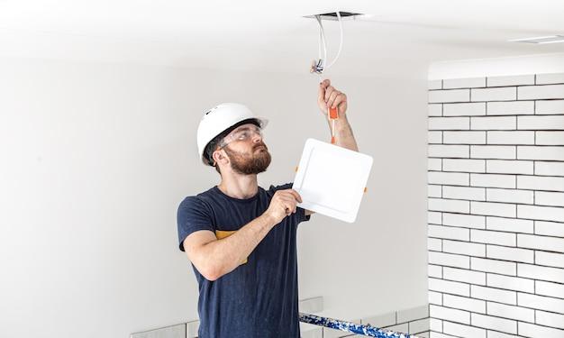 Elektriker builder mit bartarbeiter in einem weißen helm bei der arbeit, installation von lampen in der höhe. professionell in overalls mit einem bohrer auf der reparaturstelle. Kostenlose Fotos