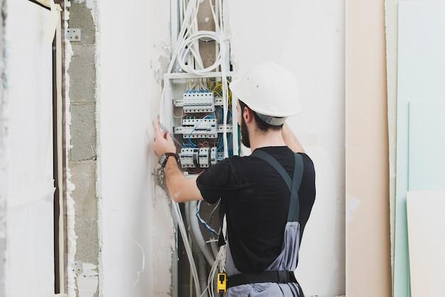 Elektriker, der mit drähten in der schalttafel arbeitet Kostenlose Fotos