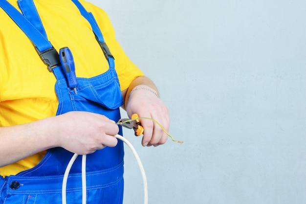 Elektriker in einem blauen overall und in einem gelben t-shirt, zangen und draht halten. Premium Fotos