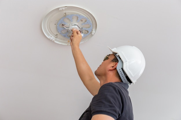 Elektriker mit weißem sturzhelm beleuchtung zur decke im haus, technikerkonzept überprüfend. Premium Fotos