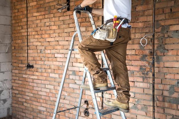 Elektriker mit werkzeugen, auf einer baustelle arbeitend. reparatur- und handwerker-konzept. Kostenlose Fotos
