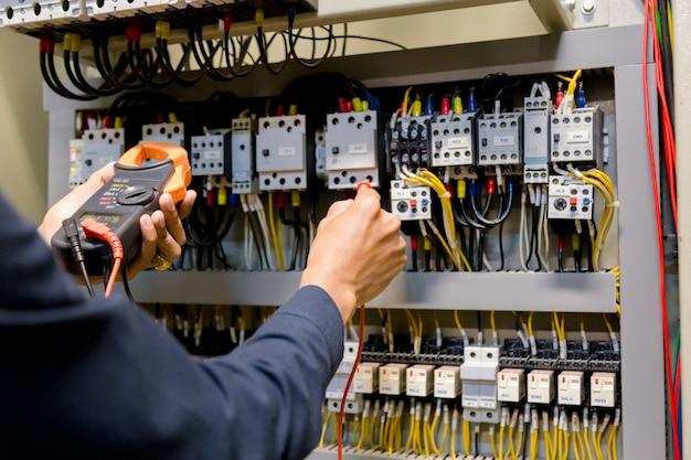 Elektrikeringenieur-arbeitstester, der spannung und strom der stromleitung in der elektroschranksteuerung misst. Premium Fotos