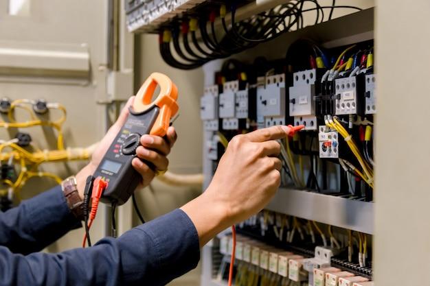 Elektrikeringenieur-arbeitstester, der spannung und strom der stromleitung misst Premium Fotos