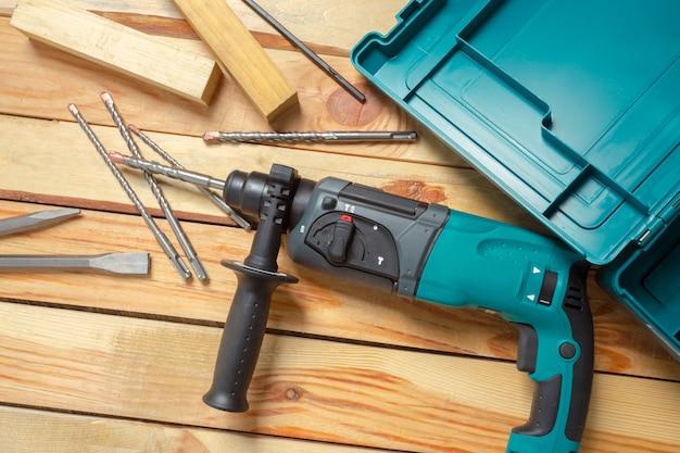 Elektrische bohrhammer liegt auf einem holztisch Premium Fotos