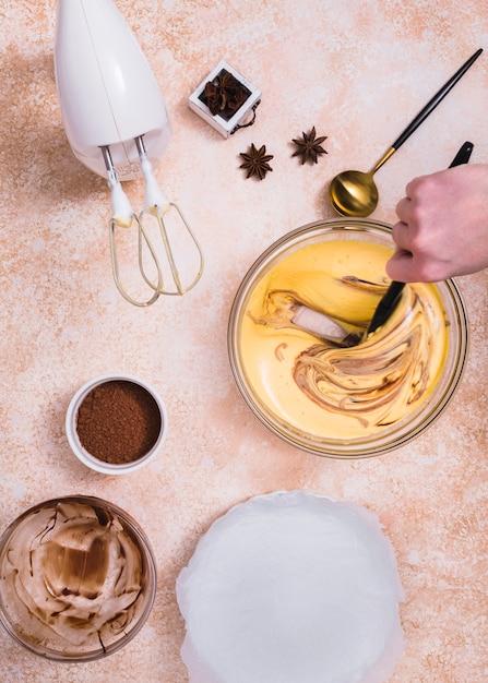 Elektrischer mixer; kakaopulver; anis und eine person, die den kuchenteig mit spachtel mischt Kostenlose Fotos