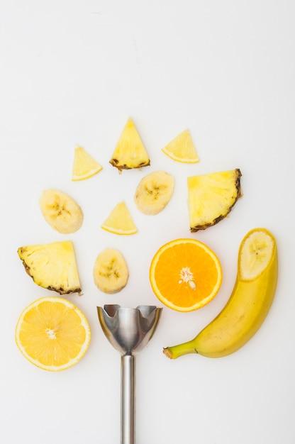 Elektrischer mixer mit ananas; bananen- und orangenscheiben isoliert auf weißem hintergrund Kostenlose Fotos