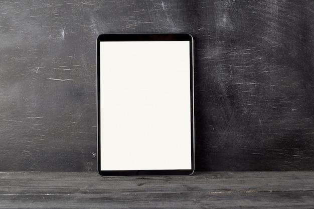 Elektronische tablette mit einem leeren weißen bildschirm gegen ein schwarzes kreidebrett Premium Fotos