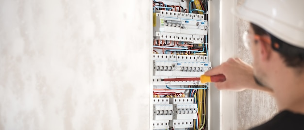 Elektrotechniker, der in einer schalttafel mit sicherungen arbeitet Kostenlose Fotos