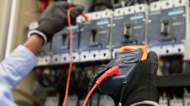 Elektrotechniker mit digitalem multimeter zur überprüfung der elektrischen stromspannung am leistungsschalter. Premium Fotos
