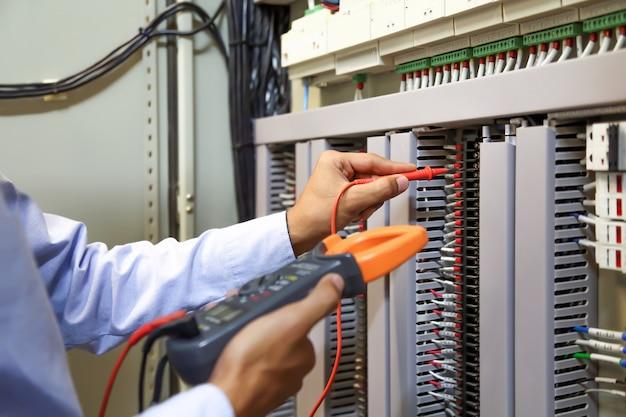 Elektrotechniker mit digitalem multimeter zur überprüfung der stromspannung am leistungsschalter. Premium Fotos