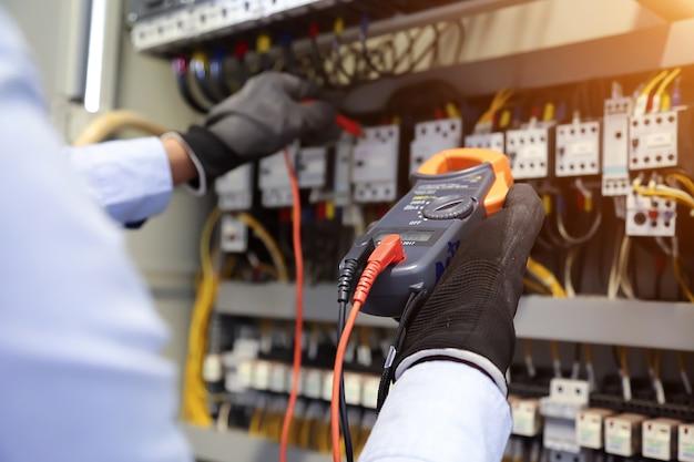 Elektrotechniker mit digitalmultimeter zur überprüfung der stromspannung am leistungsschalter im hauptverteiler. Premium Fotos