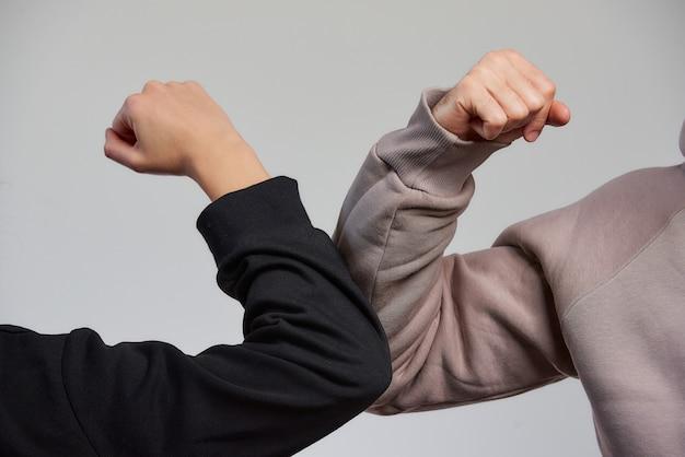 Ellenbogen stoßen. ein junge und ein mädchen in sweatshirts stoßen an die ellbogen, anstatt mit einer umarmung oder einem händedruck zu grüßen Premium Fotos