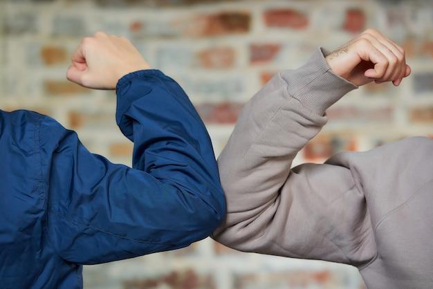Ellenbogen stoßen. ein junge und ein mädchen stoßen an die ellbogen, anstatt mit einer umarmung oder einem händedruck zu grüßen Premium Fotos