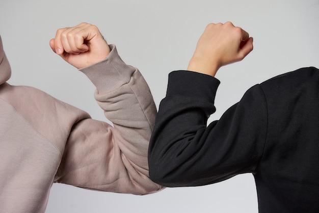Ellenbogen stoßen. eine neue art der begrüßung, um die ausbreitung des coronavirus (covid-19) zu vermeiden. ein mann und eine frau in sweatshirts stoßen an die ellbogen, anstatt mit einer umarmung oder einem händedruck zu grüßen. Premium Fotos