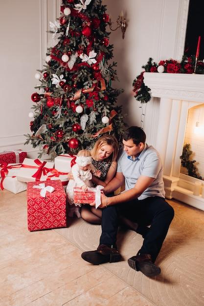 Eltern, die auf boden mit kind nahe weihnachtsbaum sitzen. Premium Fotos