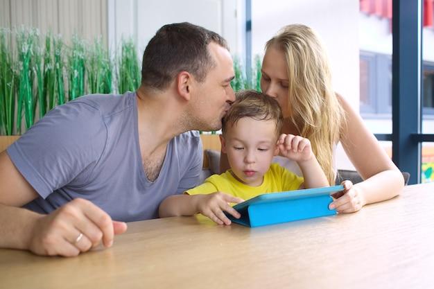 Eltern, die den sohn spielt auf auflage küssen Premium Fotos