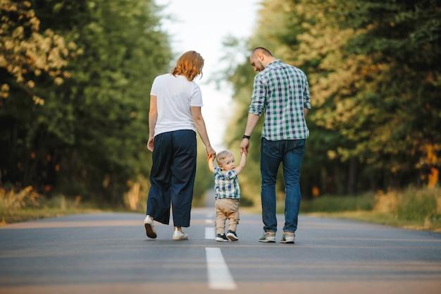 Eltern, die ihren kleinen sohn halten, gehen eine straße entlang Kostenlose Fotos