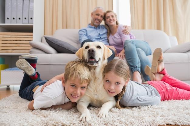 Eltern, die kinder auf wolldecke mit labrador aufpassen Premium Fotos