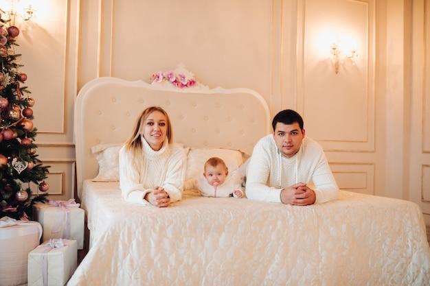 Eltern, die mit baby auf bett liegen Premium Fotos