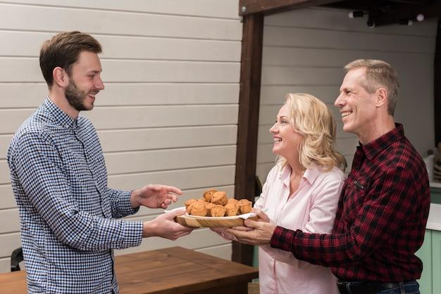 Eltern, die sohnplatte von muffins anbieten Kostenlose Fotos
