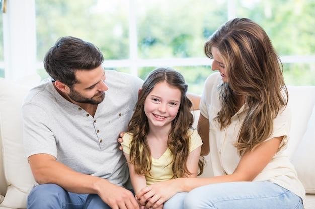 Eltern, die tochter beim sitzen auf sofa betrachten Premium Fotos