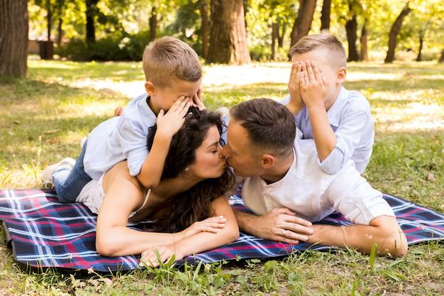 Eltern küssen sich, während kinder ihre augen bedecken