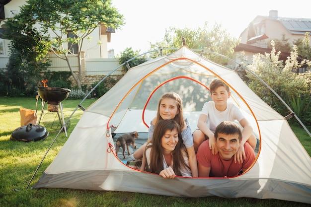 Eltern mit ihren kindern, die auf zelt während des picknicks liegen Kostenlose Fotos