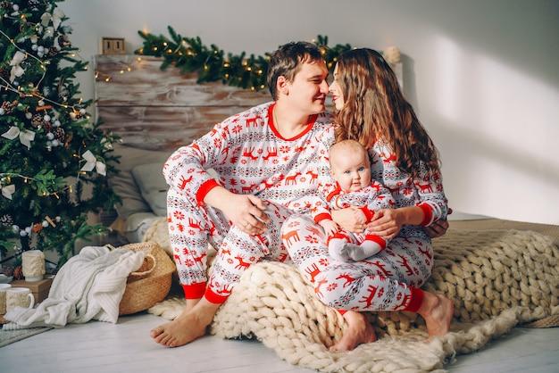 Eltern mit ihrer kleinen tochter in der feiertagskleidung mit den gedruckten rotwild und schneeflocken, die auf dem bett sitzen Premium Fotos