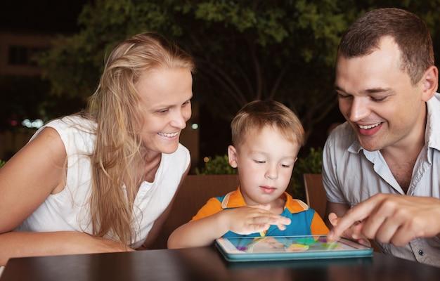 Eltern mit sohn am abend im café Premium Fotos