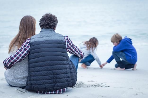 Eltern sitzen beim betrachten von kindern am strand Premium Fotos