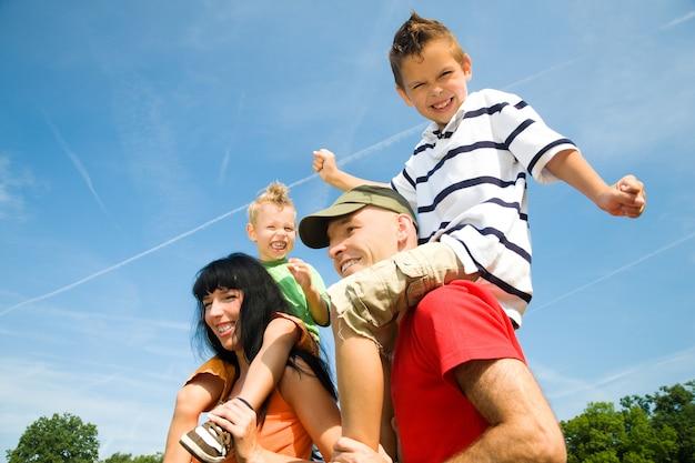 Eltern tragen ihre kinder auf den schultern Premium Fotos