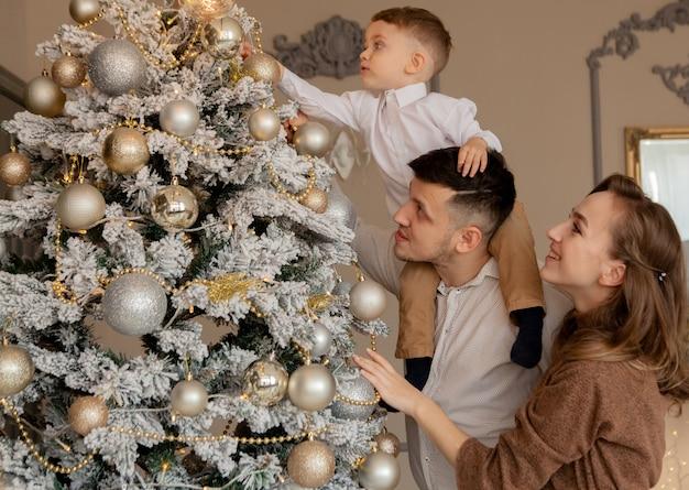 Eltern und ihr kleiner sohn schmücken den weihnachtsbaum mit spielzeug und girlanden. Premium Fotos