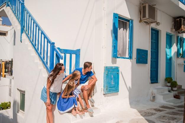 Eltern und kinder an der straße des typischen griechischen traditionellen dorfs mit weißen wänden Premium Fotos