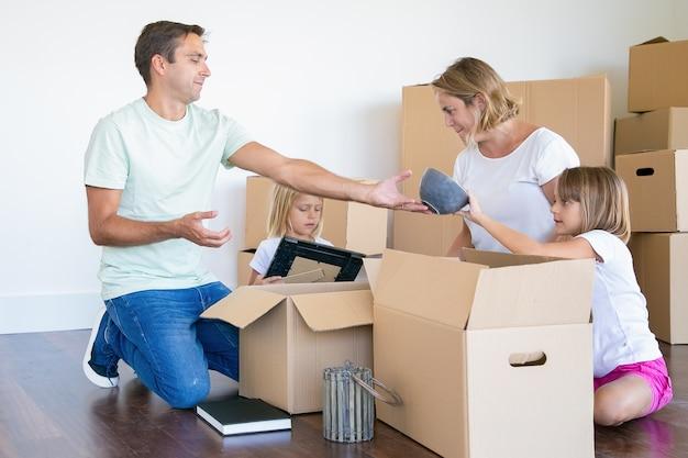 Eltern und kleine töchter packen dinge in einer neuen wohnung aus, sitzen auf dem boden und nehmen gegenstände aus offenen kisten Kostenlose Fotos