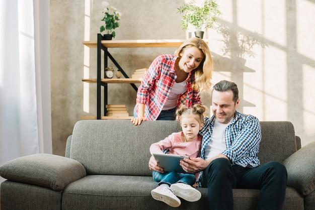 Eltern und tochter, die zu hause digitale tablette auf sofa im wohnzimmer verwendet Kostenlose Fotos