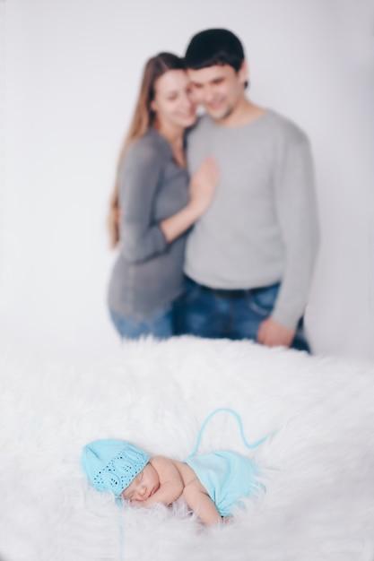 Elternschaft, kindertag, medizin, ivf-vater und mutter schauen sich das schlafende neugeborene an und streicheln es. isoliert auf weißem hintergrund Premium Fotos