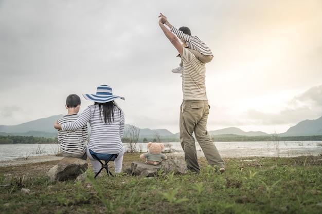 Elternteil mit jungen töchtern und sohn auf picknick nahe dem see Premium Fotos