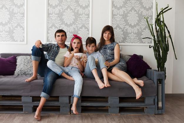 Elternteil und ihre kinder, die zusammen auf dem sofa betrachtet kamera sitzen Kostenlose Fotos