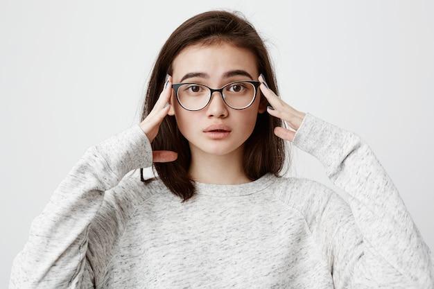Emotional besorgte frau mit dunklem haar, die eine brille trägt, die hände auf dem kopf hält und sich verwirrt und frustriert fühlt, nachdem sie das haus verlassen hat, ohne das eisen herausgezogen zu haben. menschliche emotionen und gefühle Kostenlose Fotos