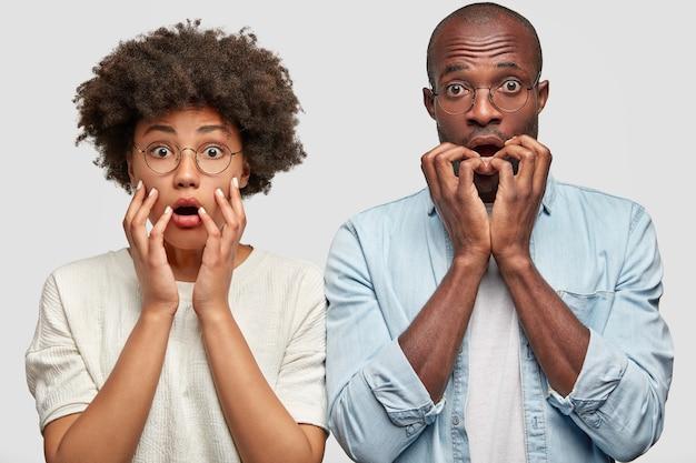 Emotional schockierte dunkelhäutige afroamerikaner sehen mit nervös verängstigten gesichtsausdrücken aus, halten die hände in der nähe des mundes, starren mit abgehörten augen, reagieren auf plötzliche unerwartete nachrichten, stehen zusammen drinnen Kostenlose Fotos