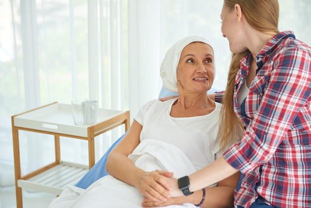 Emotional von jungen tochter weißen kaukasier mit hoffnung und lächeln besuch und ermutigen, ihre mutter zu unterstützen, die kopftuch trägt und mit brustkrebs in sauberen und klaren krankenzimmer kämpfen Premium Fotos